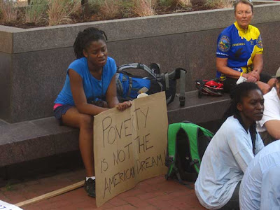 Young woman with sign reading Poverty is not the American dream