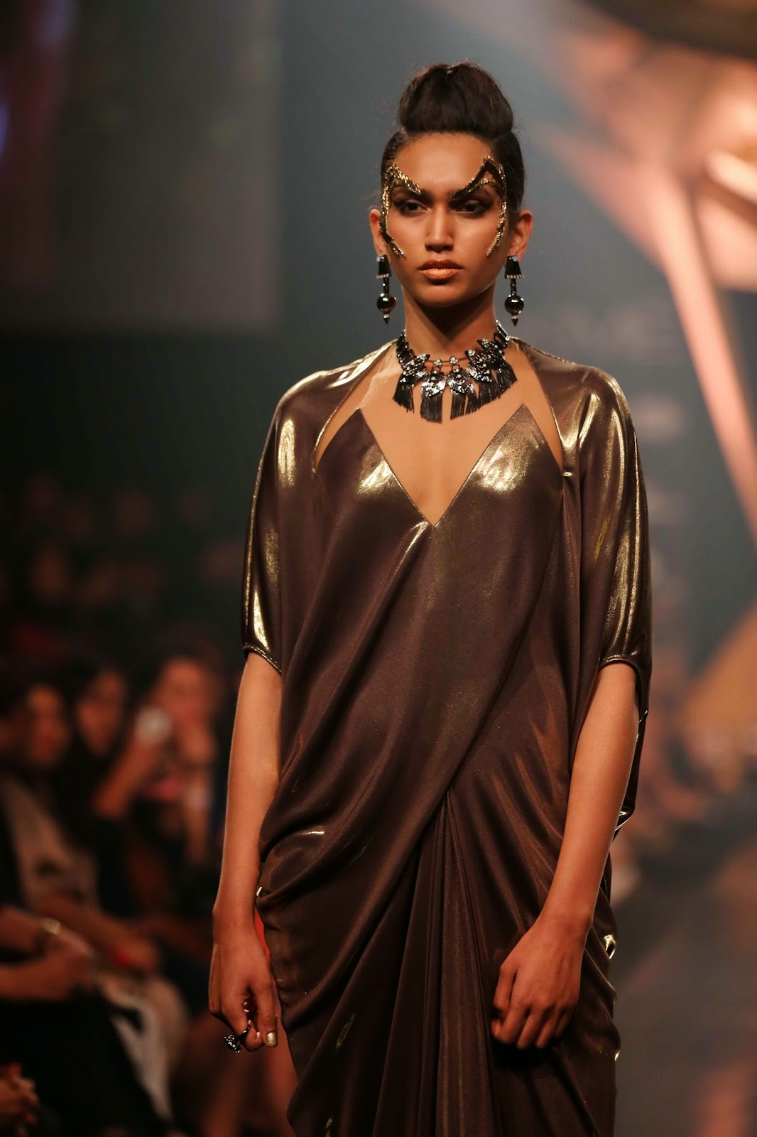 "The gold ribbed collars with a tribal centre interest, the silver multiple chains with a giant topaz pendant worn with matching bracelet, as well as danglers and the strands of diamonds framed by florets hung from a gold neck band were stunners. Ear cuffs and shoulder dusters in rustic styles along with matching bracelets completed the rich line-up of jewellery. The opulence and grandeur of the jewellery was remarkable as gold and precious gems united to create magic. Neckbands were impressively broad or detailed, while finger shields, corded neckpieces were mixed expertly to present jewels meant for a princess.   For conversation stopping statement jewellery, Mawi Keivom's ""Indian Odyssey"" collection did all the talking at Lakmé Fashion Week Summer/Resort 2014."