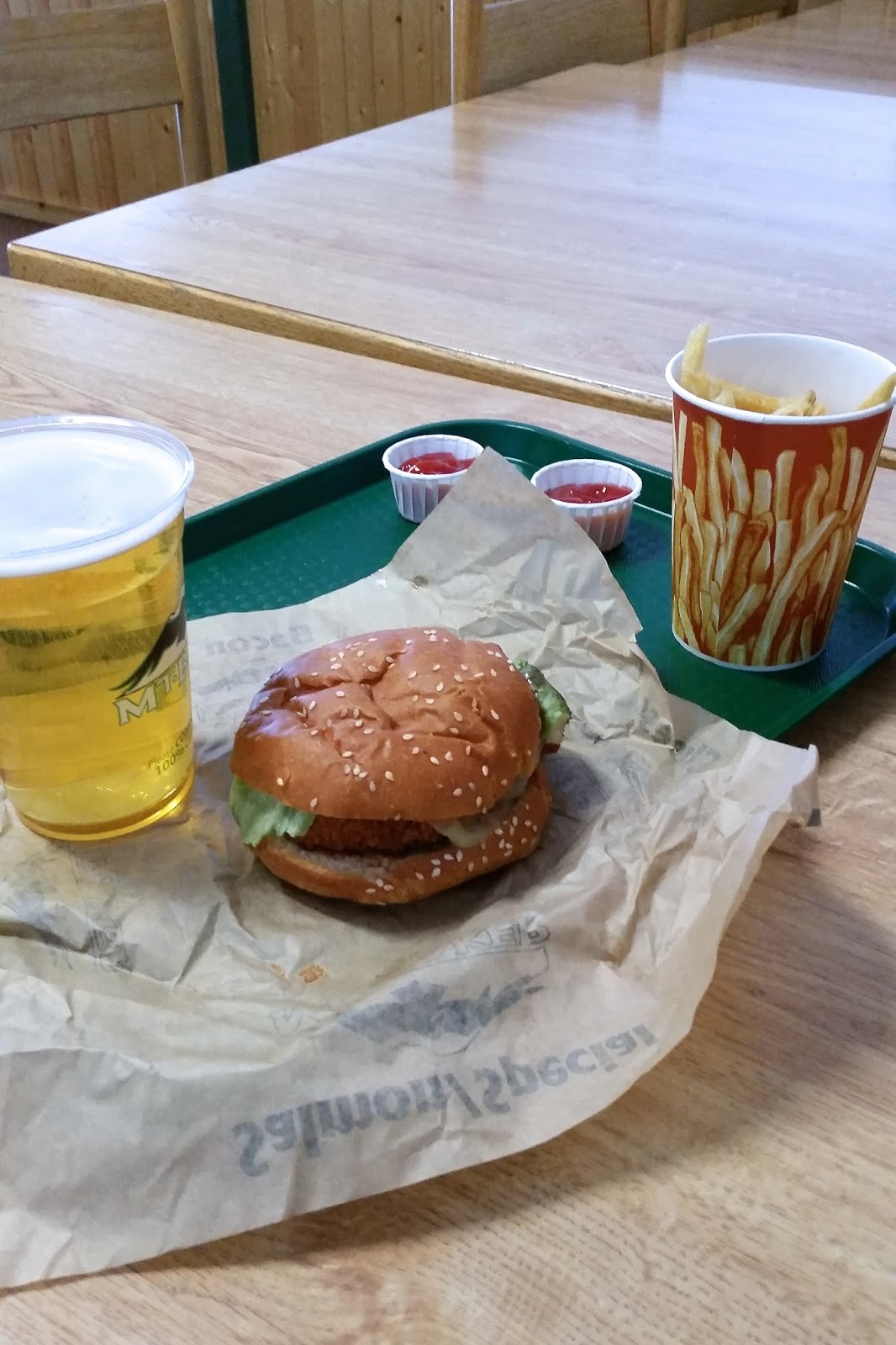chicken burger and beer on green serving tray
