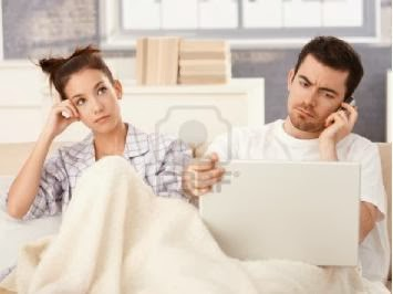 young-couple-in-bed-man-using-laptop-and-mobile-woman-bored - سبعة طرق لتنقذ بها علاقتك العاطفية من الروتين