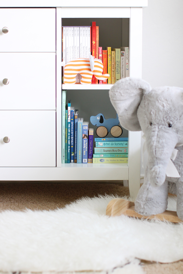 Animal-themed nursery with open shelving dresser from Land of Nod, elephant rocker from Pottery Barn Kids