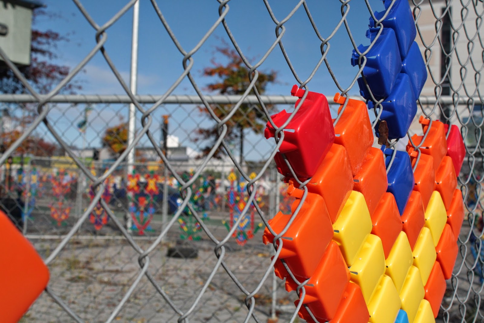 Plastic thingies stuck into hurricane fencing in the shape of flowers.