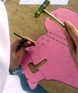 Intricate: A student busy making holes onto a wayang kulit character during the workshop.