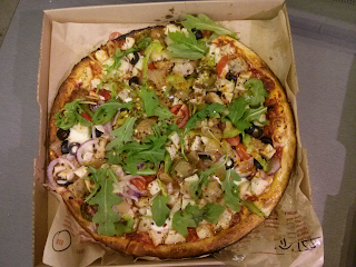 blaze pizza entire pizza with lots of toppings including chicken, tomato, onions