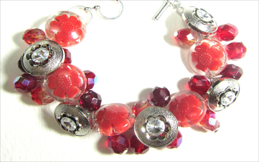 Bold bracelet has silver and red flower buttons with fire polished glass beads