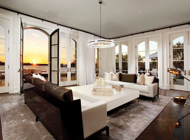 living room in an waterfront home on Harbor Island, in Newport Beach with an ocean view, french doors, dark wood floors, dueling modern white and brown sofas, white floor length curtains, a large square coffee table, and a small chandelier