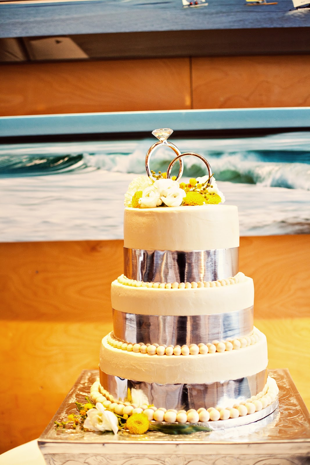 http://3.bp.blogspot.com/-EIVaWvXKIgA/Te20x-6RbAI/AAAAAAAADQ0/chqm432LpYY/s1600/modern%20beach%20wedding%20metallic%20wedding%20cake%20with%20yellow%20button%20mums.jpg