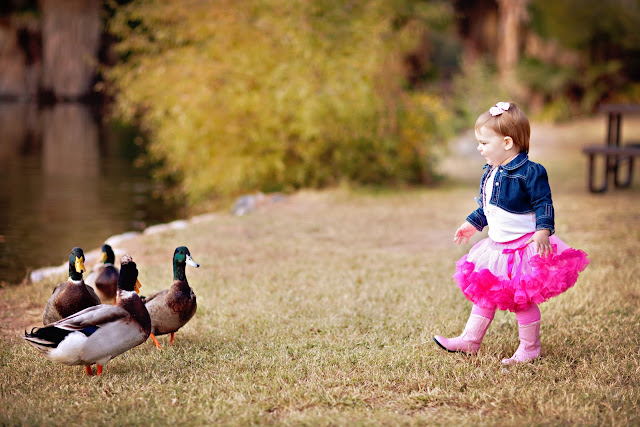 Little girl wearing tutu feeding ducks by pond during birthday session
