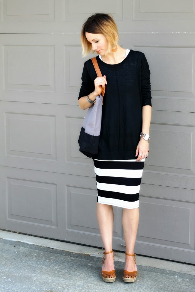 Long black sweater, striped knit skirt and clogs
