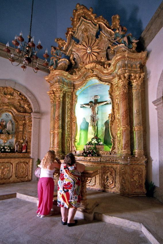Duas mulheres em oração no altar da capela