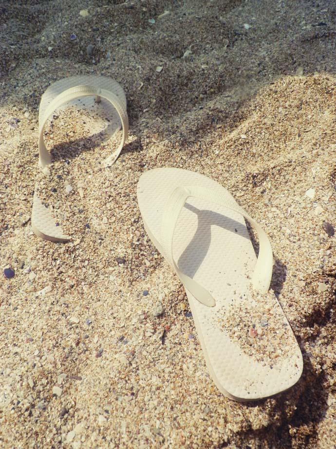 White flip flops in the sand on the beach in Sozopol, Bulgaria