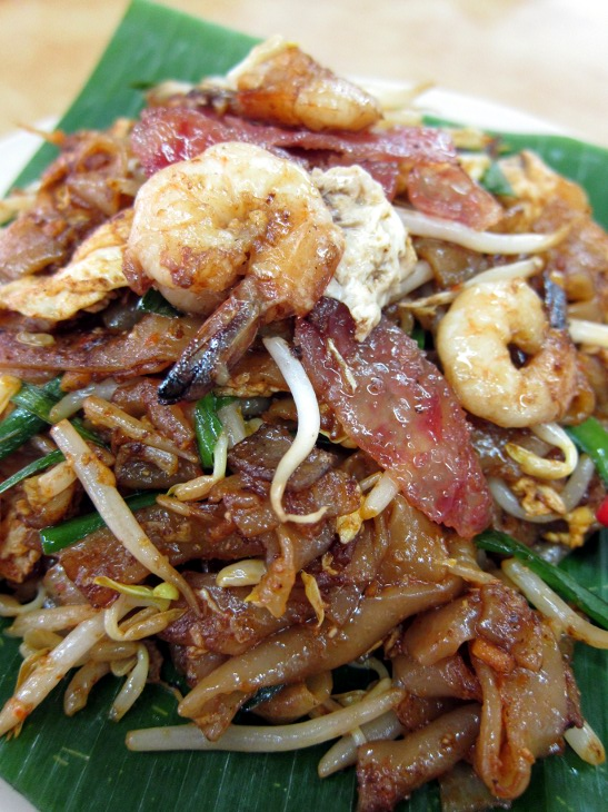 Char kuey teow – flat noodles with prawns, chinese sausage, beansprouts and spring onions at a hawker centre somewhere in PJ. Malaysian hawker stall food fest.