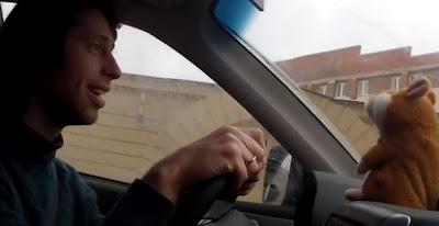 hombre con un muñeco que habla en su auto
