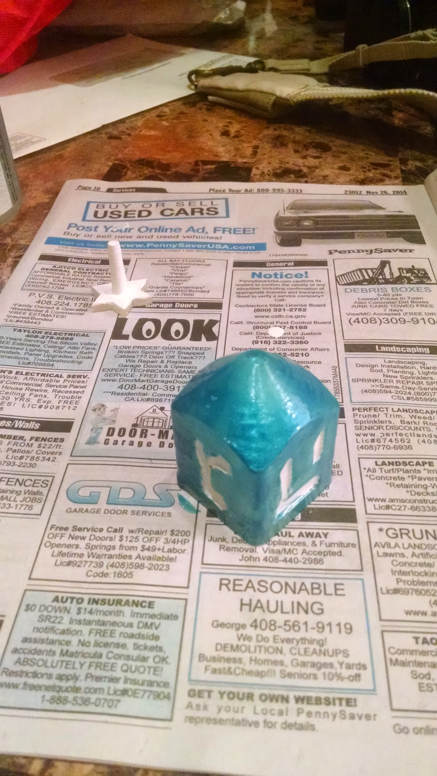 dreidel is lying on newsprint with the tip pointing up and the handle separate. The surface is a shiny translucent blue.
