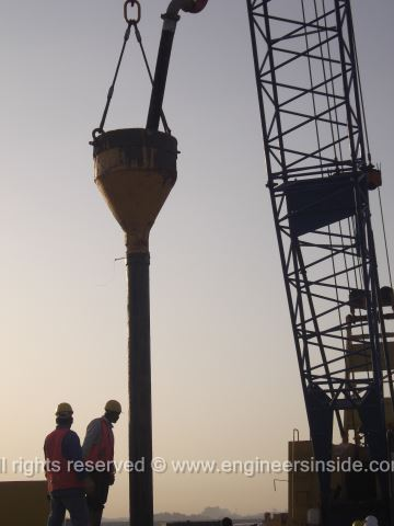 Workers and the crane pouring concrete into test pile