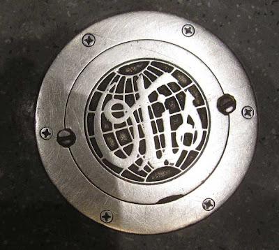 Worn steel Otis logo, globe shape, script letters