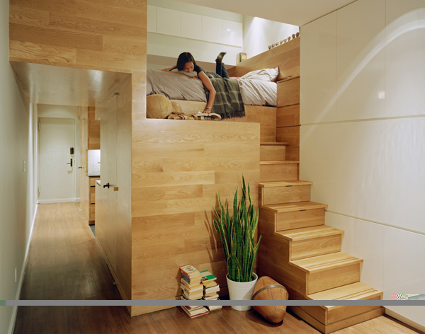 Photo of wooden stairs leading to elevated bed as seen from living area