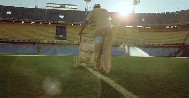 Hombre pintando las rayas de un campo de fútbol