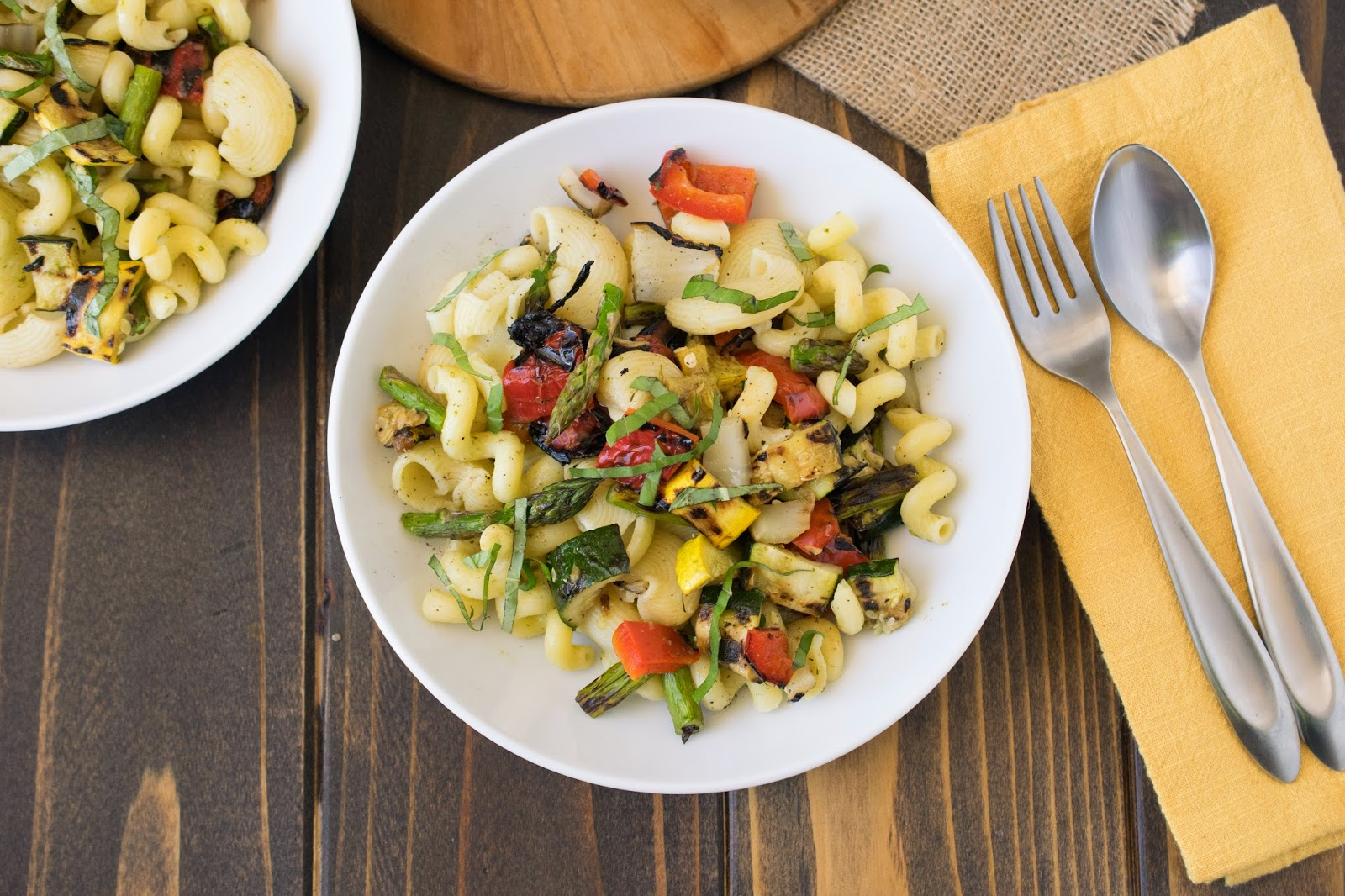 Grilled Spring vegetable pasta salad in a white bowl with a fork and spoon and a gold napkin