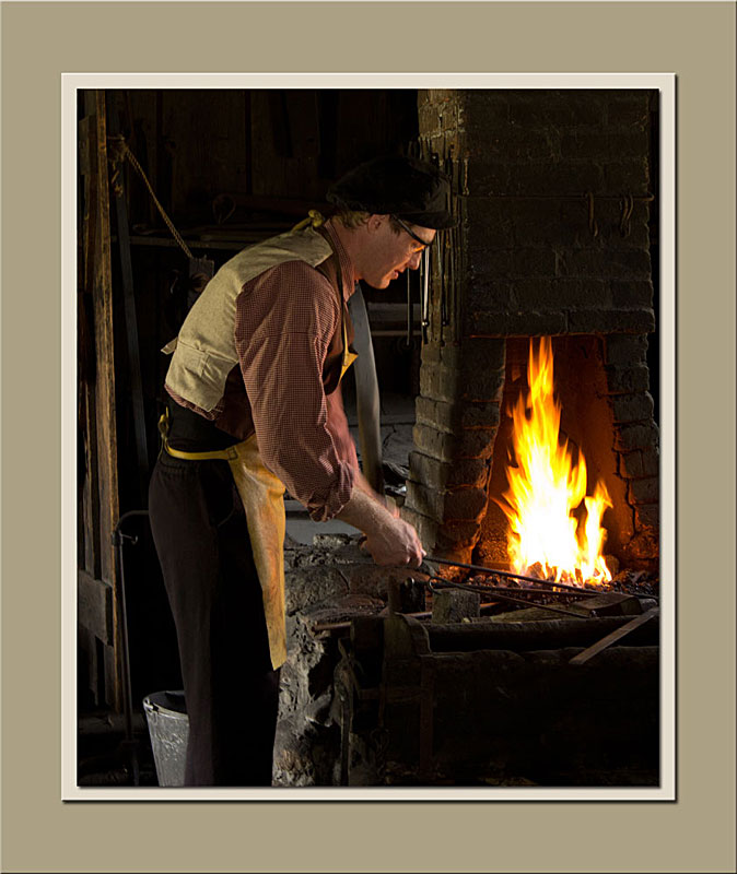 The blacksmith at Black Creek Pioneer Village stoking the fire.  Holly Cawfield Photography