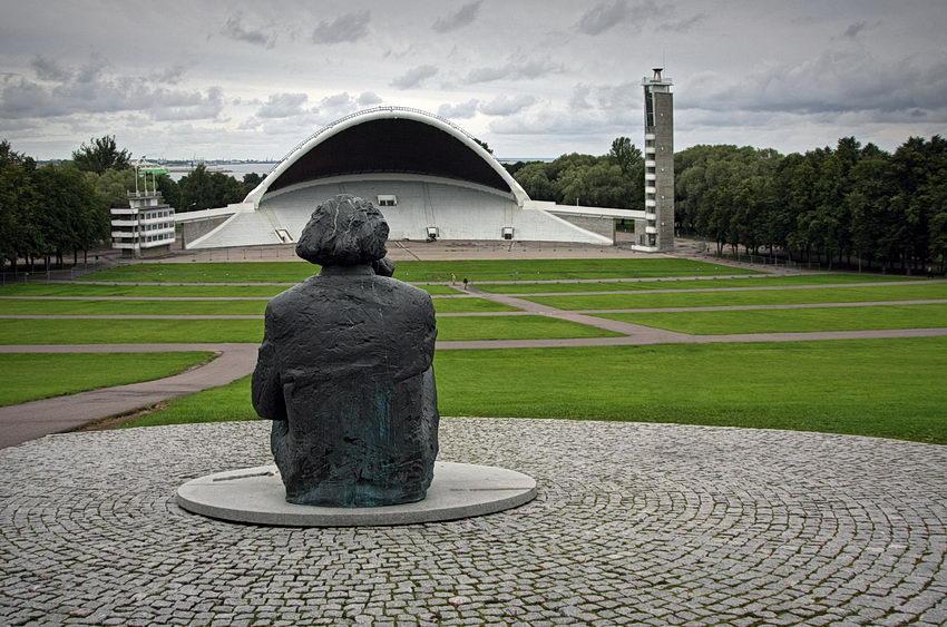 Foto do Campo das canções com o monumento a Gustav Ernesaks em primeiro plano, de costas