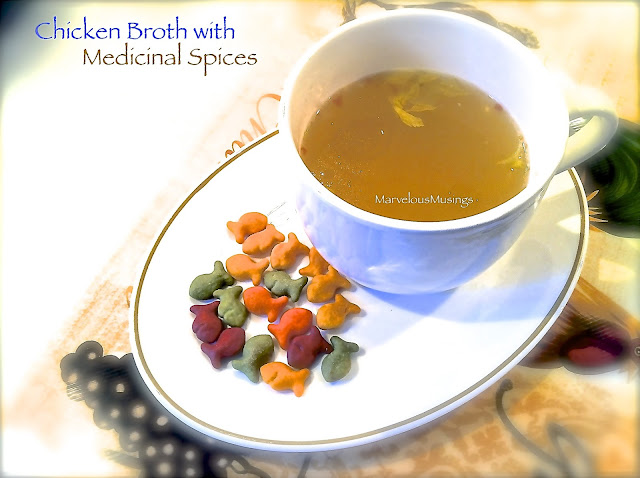 Chicken Broth with Medicinal Spices plated in bowl with goldfish colors crackers on the side marvelous musings