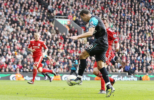 Arsenal captain Robin van Persie shoots to score the winner against Liverpool