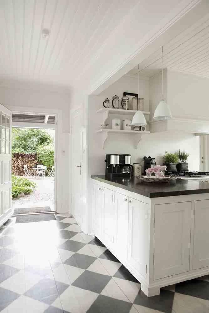 Podłoga z desek pomalowana w czarno-białe karo, białe meble kuchenne z czarnym blatem skandynawski design w kuchni