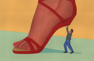 A small man supporting a woman's heel of her shoe