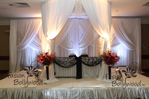 white draping gazebo with damask touch with red orchid arrangement