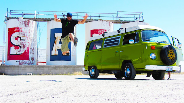 Jumping through the air next to a Volkswagen van in front of silos that spell out SAVE. Somewhere in Idaho.