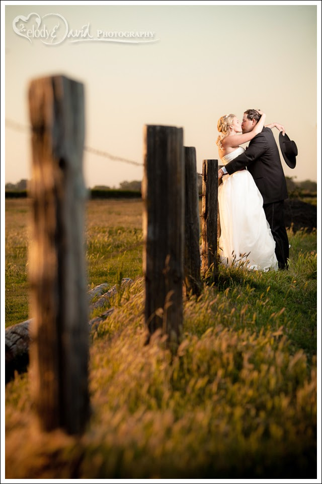Couple poses against barbed wire fence at susnset