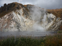 Larger sulfurous hot pond near noboribestu-onsen emitting some steam with white hill in background with trees on the top