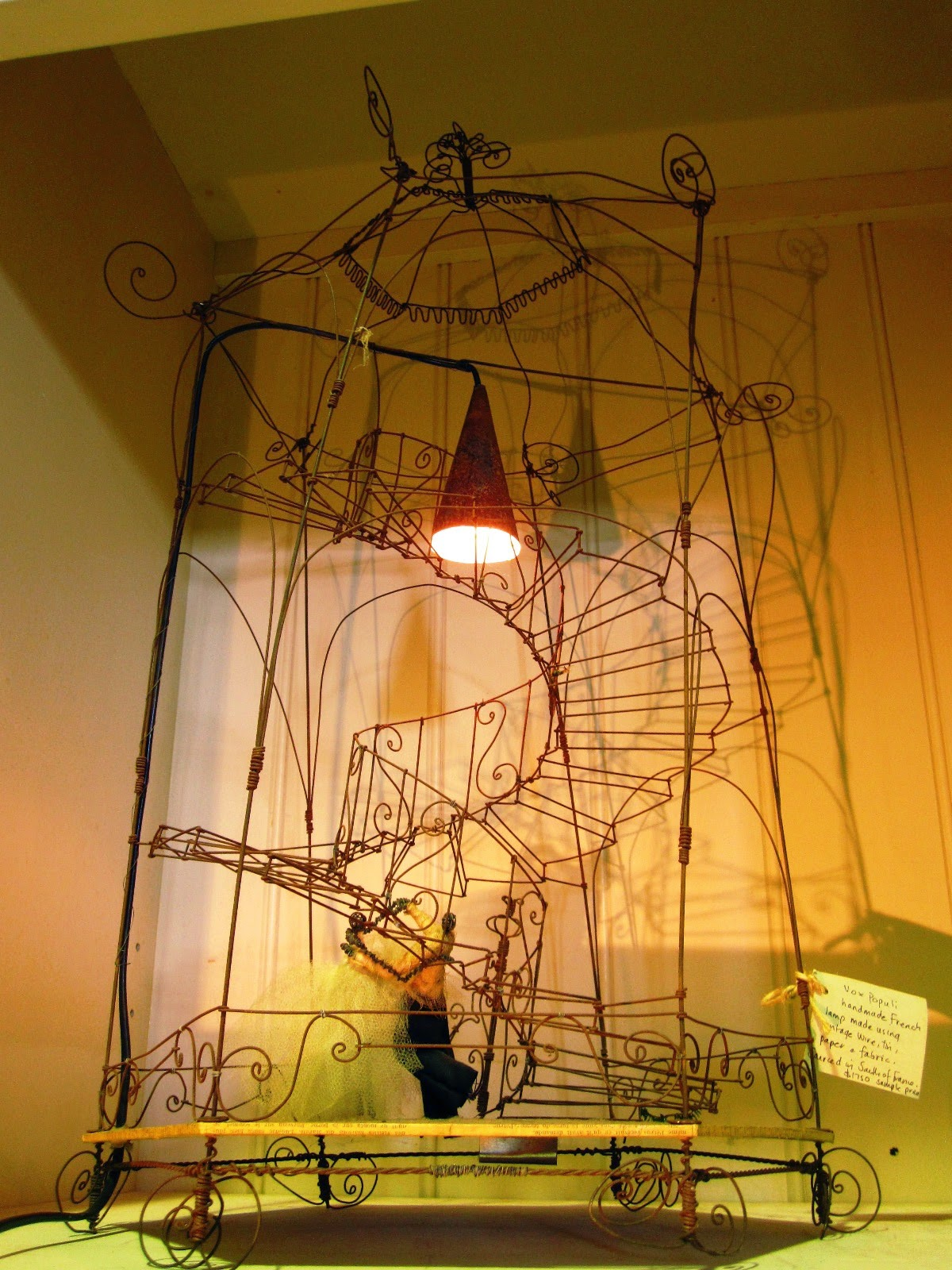 Vintage wire birdcage-shaped sculpture with wire spiral staircase and fabric doll, used as the basis for a lamp.