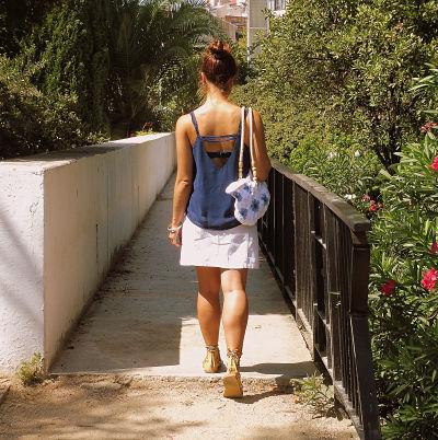 Chica de espaldas andando con un bolso de granny square de flor africana