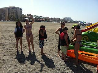 En la imagen se ven a varios niños colocándose el chaleco salvavidas, mientras los demás saludan a cámara