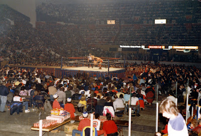 Dino Bravo bodyslams Tony Garea at Toronto's Maple Leaf Gardens during a WWF wrestling matinee on Dec. 28, 1986. A wide shot from the corner golds showing the MLG wrestling ring, ramp and overhead scoreboard lights.