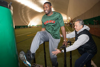 Rafael assists David during a recent conditioning day at the Dome. (Photo by Philip Hall/University of Alaska Anchorage)