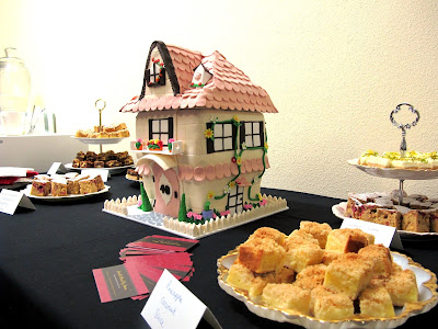 Table of slices with a dolls'-house shaped cake in the middle.