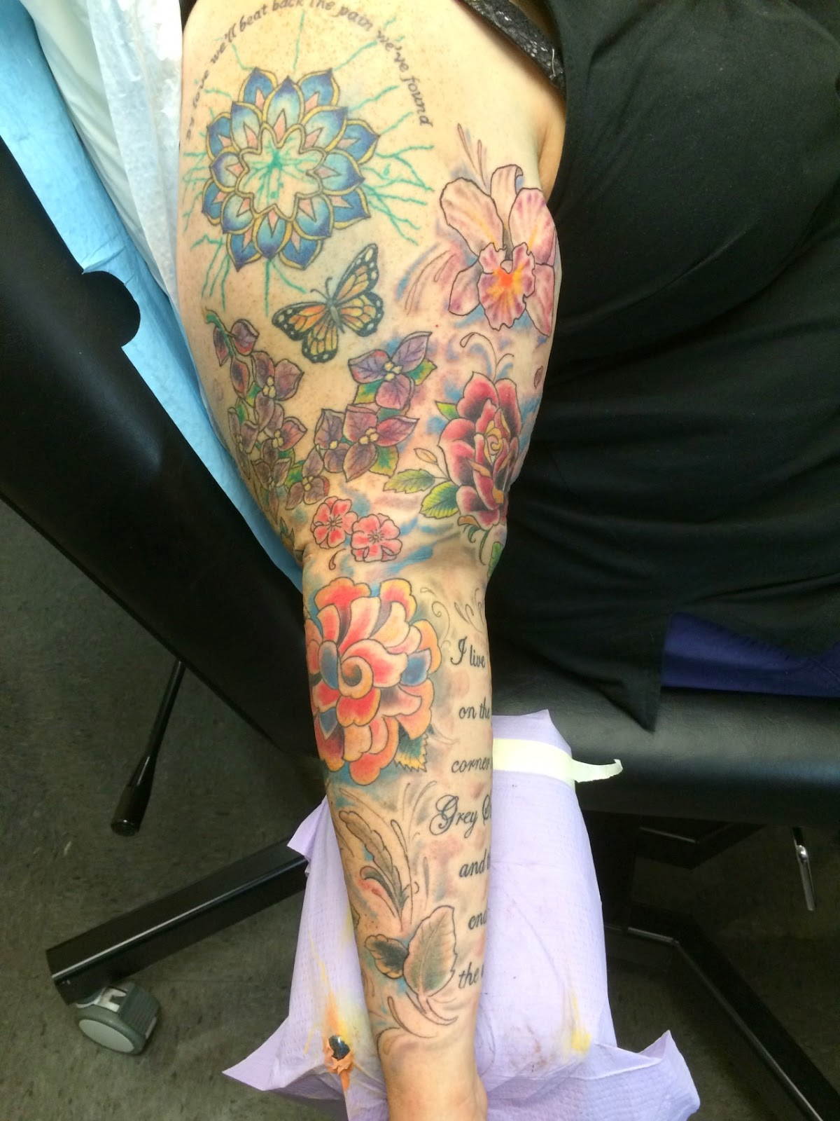 "Photograph: A tattooed arm. At top is a lotus with the words ""By love we'll beat back the pain we've found."" Below are a butterfly and a sprig of bougainvillea. To the right of that are an orchid and a red. Below these are two cherry blossoms, a cabbage rose, and some leaves and swirls of colour. To the side some words start to become visible."