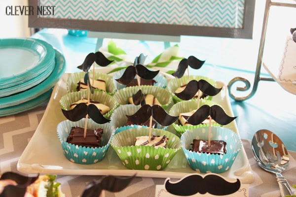 tablescape idea for mustache themed babyshower. Framed art doubles as nursery decor. Clever Nest #turquoisegraylime #littleman #hipsterbabyshower #glasses #bowtie #clevernest #bowtienapkins #babyshowergame
