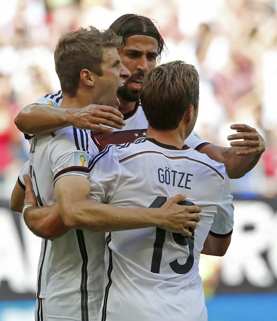 Germany's Thomas Mueller, left, celebrates with Mario Goetze after scoring the opening goal during the group G World Cup soccer match between Germany and Portugal at the Arena Fonte Nova in Salvador, Brazil, Monday, June 16, 2014.
