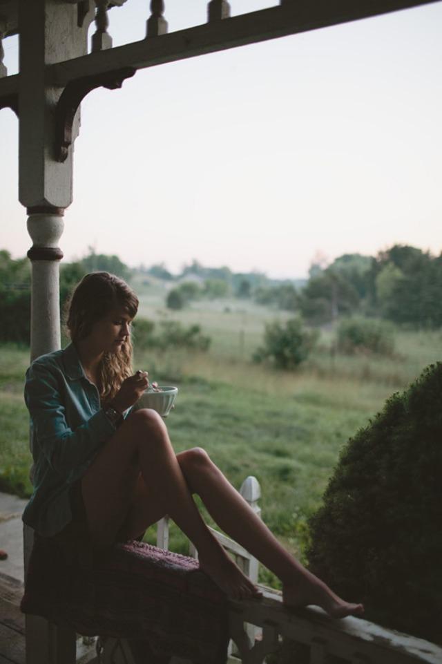 chica desayunando en porche