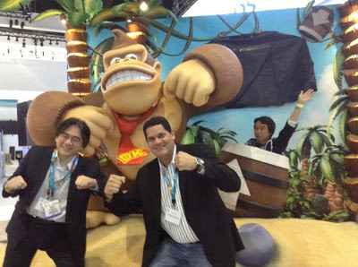A picture of Reggie and Iwata standing in front of Donkey Kong with Miyamoto trolling in the back