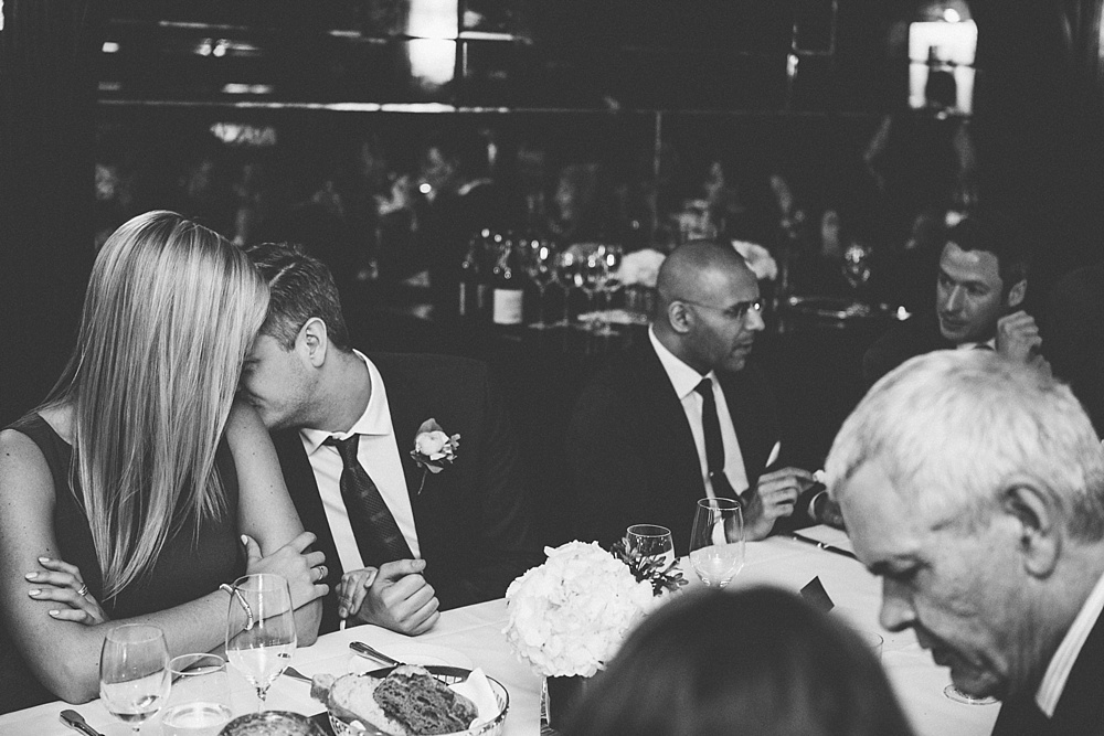 man kisses his girlfriend at wedding reception beautiful black and white candid photograph