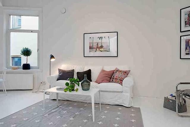 Widok na białą sofę z szarymi i kolorowymi poduchami