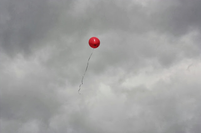 Red balloon floating into grey sky