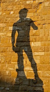 (Shadow of Michaelangelo's David on brick wall.)