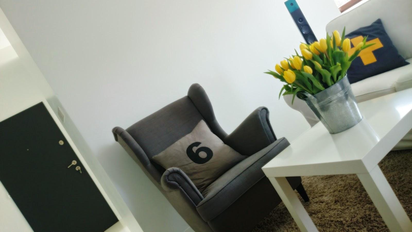 Bie ściany i grafitowe drzwi, szary fotel, białe wnętrze, żółte tulipany w ocynkowanym wiadrze