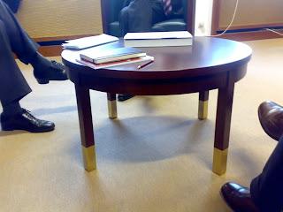 Hosen- und Tischbeine im Regierungsviertel (Ergänzung: Die Hosenbeine und Schuhe gehören offensichtlich zu Männern)